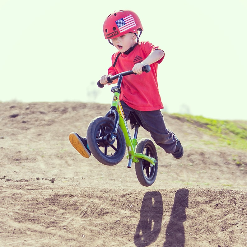 Kid with Strider Balance Bike on terrain with woops